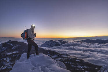 Mountaineer on the mountain summit during twilight, Orobie Alps, Lecco, Italy - MCVF00168