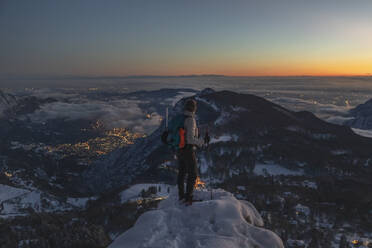 Mountaineer on the mountain summit during twilight, Orobie Alps, Lecco, Italy - MCVF00171