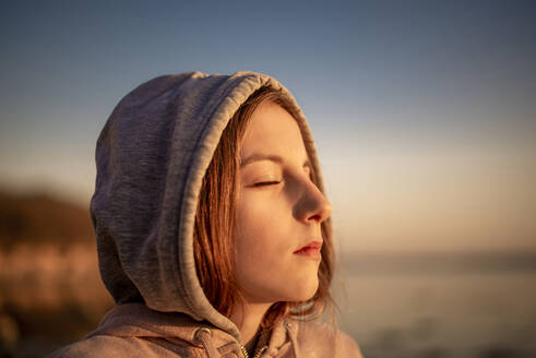 Germany, Mecklenburg-West Pomerania, Poel Island, Close-up of teenage girl with eyes closed on beach at sunset - BFRF02167