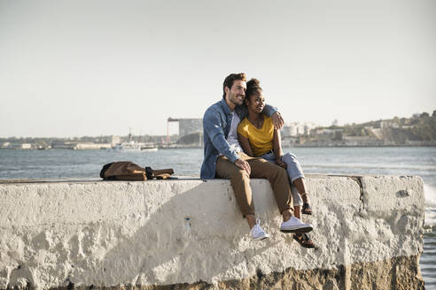 Young couple sitting on pier at the waterfront enjoying the view, Lisbon, Portugal - UUF19843