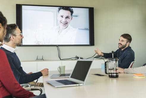 Business people having a video conference in boardroom - UUF19930