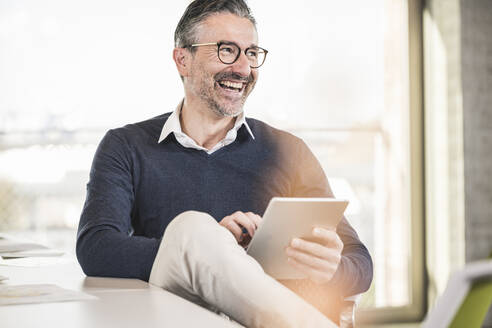 Laughing mature businessman sitting at desk in office holding tablet - UUF20002