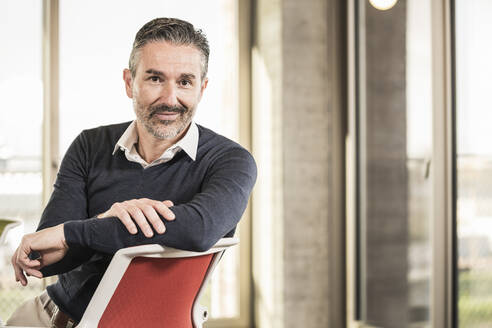 Portrait of a confident mature businessman sitting on chair in office - UUF20008