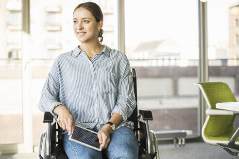 Young businesswoman with tablet sitting in wheelchair in office - UUF20014