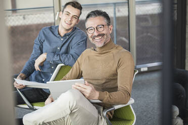 Portrait of happy mature businessman with tablet and young man in office - UUF20026