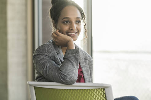 Smiling young businesswoman sitting on a chair in office - UUF20035