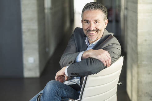 Portrait of a smiling mature businessman sitting on chair in office - UUF20044