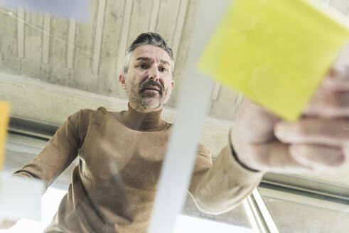 Mature businessman working on adhesive notes on glass table in office - UUF20050