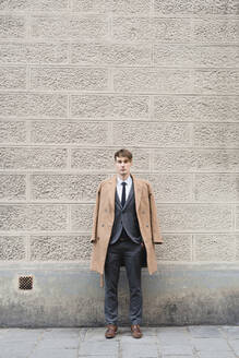 Portrait of young businessman standing on pavement - FMOF00858