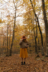 Fashionable redheaded young woman in autumnal forest covering her face with hat - AFVF04887