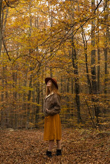 Fashionable redheaded young woman exploring autumnal forest - AFVF04890