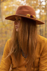 Portrait of fashionable redheaded young woman wearing felt hat in autumnal forest - AFVF04893