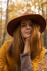 Portrait of fashionable redheaded young woman in autumnal forest - AFVF04896