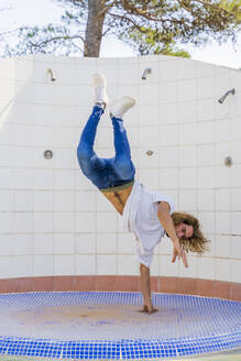 Young man doing handstand on one hand - AFVF04917