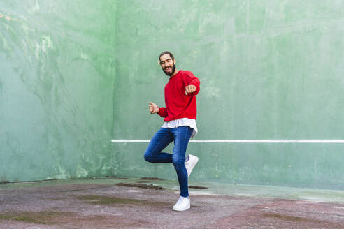 Portrait of bearded young man dancing in front of green wall - AFVF04923