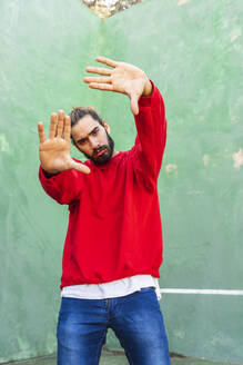 Portrait of serious young man wearing red sweatshirt raising hands in front of green wall - AFVF04926