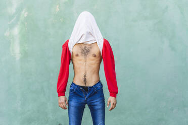 Young man covering head with his t-shirt in front of green wall - AFVF04932