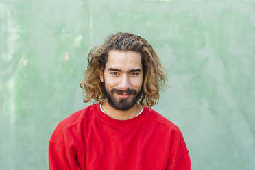 Portrait of bearded young man wearing red sweatshirt in front of green wall - AFVF04935