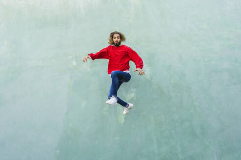 Portrait of young man wearing red sweatshirt jumping in the air in front of green wall - AFVF04938