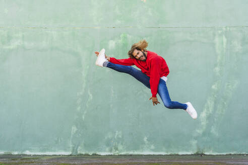 Portrait of young man in wearing red sweatshirt jumping in the air in front of green wall - AFVF04941