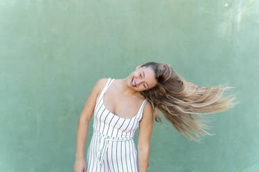 Blond young woman tossing her hair in front of green wall - AFVF04953