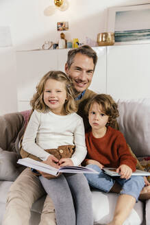 Portrait of happy father reading book with daughters on couch - MFF04969
