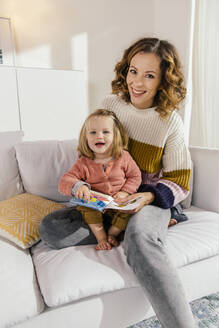 Portrait of happy mother and little daughter with book on couch at home - MFF04978