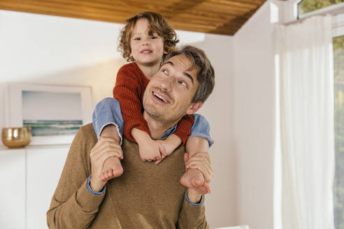 Father carrying daughter on shoulders at home - MFF04981