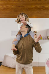 Happy father carrying daughter on shoulders at home - MFF04984