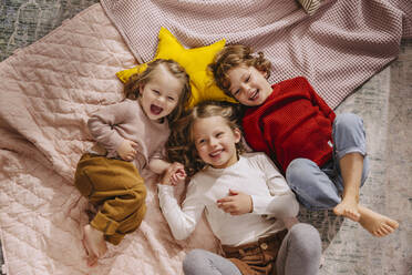 Three happy girls lying on blankets at home - MFF04987