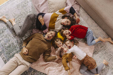 Happy family with three daughters lying on blankets at home - MFF04990