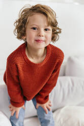 Portrait of smiling girl standing on couch at home - MFF04996