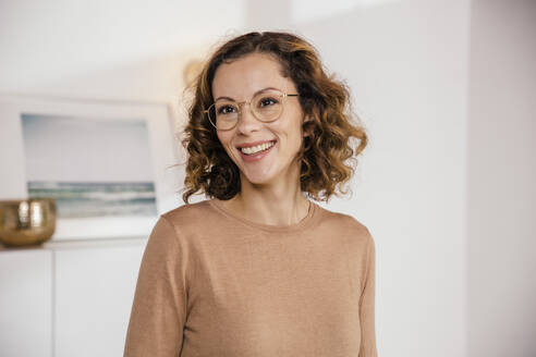 Portrait of smiling brunette woman with glasses at home - MFF05002
