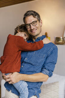 Portrait of smiling father carrying daughter at home - MFF05011