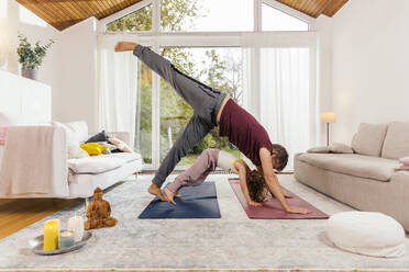 Father and daughter doing yoga together at home - MFF05014