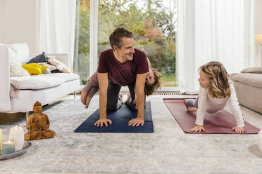 Father with daughters doing yoga in living room at home - MFF05017