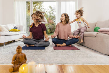 Exuberant girls with parents meditating at home - MFF05020