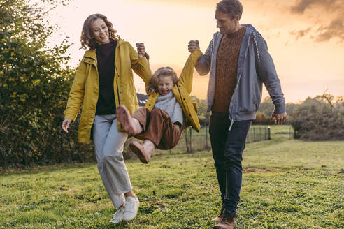 Parents lifting up daughter on a meadow in autumn - MFF05026