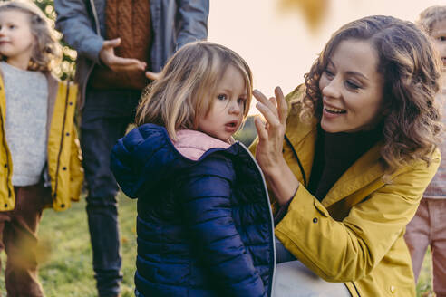 Happy mother with daughter and family outdoors in autumn - MFF05032