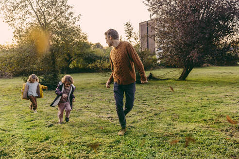 Father running with daughters on a meadow in autumn - MFF05044