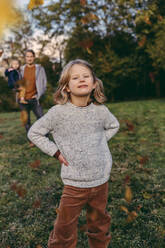 Portrait of confident girl with her family on a meadow in autumn - MFF05047