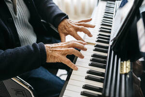Crop view of senior man playing piano - JRFF03964