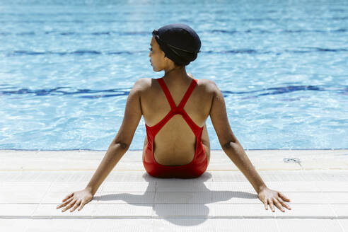 Back view of young woman wearing red swimsuit and swimming cap relaxing at poolside after swimming - SODF00459