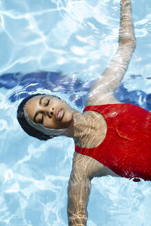 Portrait of young woman with eyes closed floating on water in swimming  pool - SODF00465