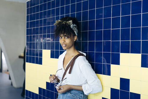 Portrait of young woman with curly black hair leaning against tiled wall - SODF00477