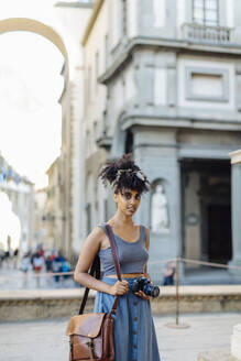 Portrait of young woman with camera exploring the city, Florence, Italy - SODF00498