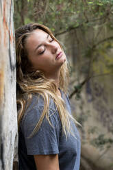 Young blond woman leaning on a wall, closed eyes - AFVF04960
