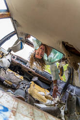 Young blond man in junk car, upside down - AFVF04963