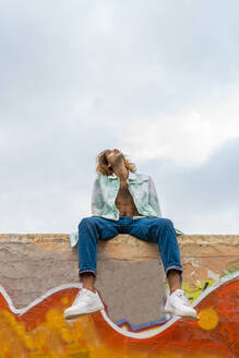 Young blond man sittung on a wall and looking up - AFVF04972
