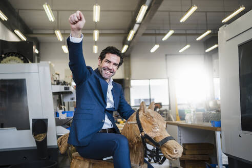 Portrait of a playful businessman on wooden rocking horse in a factory - DIGF09049